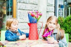 Niños que se divierten al aire libre, descansando en un café imagen de archivo