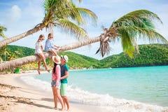 Niños que se divierten que se sienta en la palmera Familia feliz que se relaja en la playa tropical de la bahía de Carlisle con l Imágenes de archivo libres de regalías