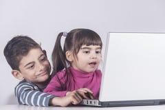 Niños que se divierten usando un ordenador portátil Imágenes de archivo libres de regalías