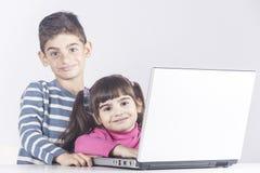 Niños que se divierten usando un ordenador portátil Fotos de archivo libres de regalías