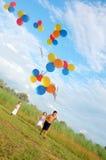 Niños que se ejecutan con los globos Fotografía de archivo