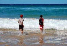 Niños que se ejecutan en el océano fotografía de archivo libre de regalías