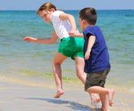 Niños que se ejecutan en la playa Imagen de archivo libre de regalías