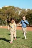 Niños que se ejecutan en parque Imagen de archivo