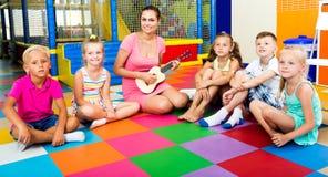 Niños que se sientan alrededor de profesor con la pequeña guitarra Imagenes de archivo
