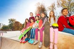 Niños que se sientan con los monopatines y el casco Imágenes de archivo libres de regalías