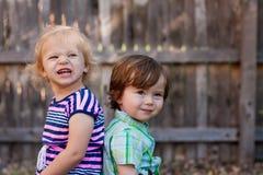 Niños que se sientan de nuevo a la parte posterior Foto de archivo libre de regalías