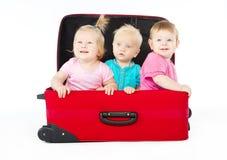 Niños que se sientan dentro de la maleta roja fotografía de archivo