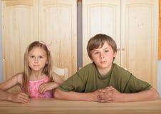 Niños que se sientan detrás de la tabla de madera imágenes de archivo libres de regalías