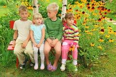 Niños que se sientan en banco en jardín Imagenes de archivo