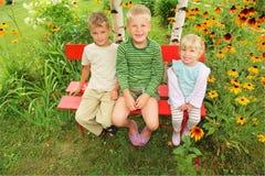 Niños que se sientan en banco en jardín Imagen de archivo