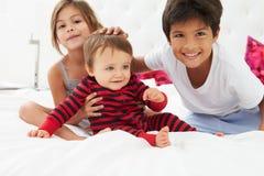 Niños que se sientan en cama en pijamas junto Imágenes de archivo libres de regalías