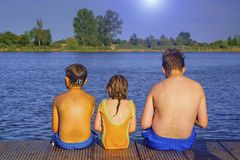 Niños que se sientan en el embarcadero Verano y concepto de la niñez Niños en el lago imagenes de archivo