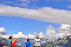 Niños que se sientan en el punto de vista en montañas Foto de archivo
