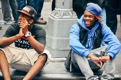 2 niños que se sientan en el Times Square, Manhattan Imagen de archivo