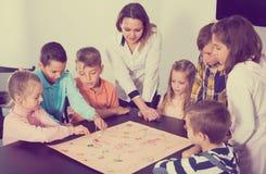 Niños que se sientan en la tabla con el juego de mesa y los dados en escuela Imágenes de archivo libres de regalías