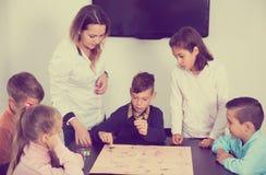 Niños que se sientan en la tabla con el juego de mesa y los dados en la clase Foto de archivo libre de regalías