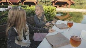 Niños que se sientan en la tabla en el café al aire libre metrajes