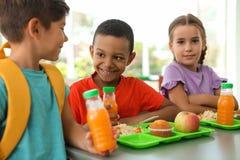 Niños que se sientan en la tabla y que comen la comida sana durante rotura imagenes de archivo