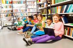 Niños que se sientan en piso en biblioteca y estudiar Fotos de archivo