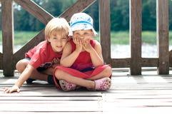 Niños que se sientan en un embarcadero Fotografía de archivo