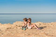 Niños que se sientan en una orilla de mar imagen de archivo