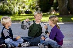 Niños que se sientan y que hablan junto en la calzada Imagen de archivo