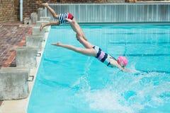 Niños que se zambullen en agua en el poolside Fotos de archivo libres de regalías