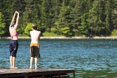 Niños que se zambullen en el lago Fotos de archivo