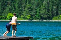 Niños que se zambullen en el lago Fotos de archivo libres de regalías