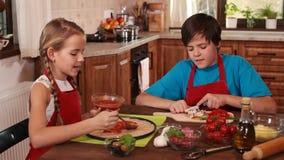 Niños que separan la salsa en la pasta de la pizza y que preparan los ingredientes almacen de metraje de vídeo