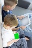 Niños que sientan y que usan la tableta y el teléfono elegante móvil con la pantalla verde en casa foto de archivo
