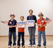 Niños que sostienen el indicador americano y que desgastan los sombreros Foto de archivo libre de regalías