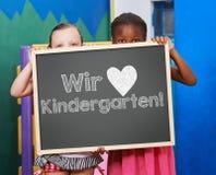 Niños que sostienen la pizarra con lema alemán fotos de archivo libres de regalías