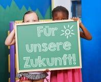 Niños que sostienen la pizarra con lema alemán imagenes de archivo