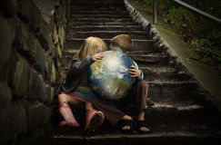 Niños que sostienen la tierra Planetin secreta Fotografía de archivo
