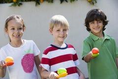 Niños que sostienen los huevos en las cucharas para la raza del huevo imagen de archivo libre de regalías