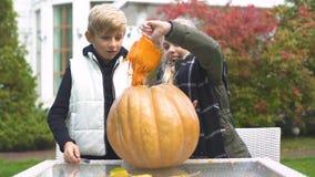 Niños que tallan la Jack-o-linterna de la calabaza, emocionada con proceso, emociones felices almacen de metraje de vídeo