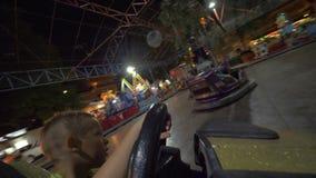 Niños que tienen buen tiempo en la feria de diversión al conducir los coches de parachoques almacen de metraje de vídeo