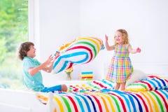 Niños que tienen lucha de almohada Foto de archivo
