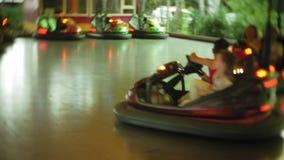 Niños que tienen un paseo en el coche de parachoques en el parque de atracciones almacen de metraje de vídeo
