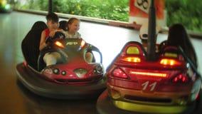 Niños que tienen un paseo en el coche de parachoques en el parque de atracciones almacen de video
