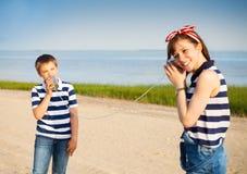 Niños que tienen una llamada de teléfono con las latas Imagen de archivo libre de regalías