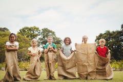Niños que tienen una raza de saco Imagenes de archivo