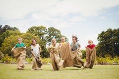 Niños que tienen una raza de saco en parque Foto de archivo