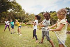 Niños que tiran de una cuerda en esfuerzo supremo Imágenes de archivo libres de regalías