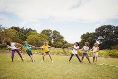 Niños que tiran de una cuerda en esfuerzo supremo Fotos de archivo libres de regalías