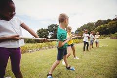 Niños que tiran de una cuerda en esfuerzo supremo Foto de archivo