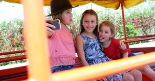 Niños que toman el selfie con el teléfono móvil en el jardín 4k almacen de metraje de vídeo