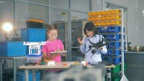 Niños que trabajan en un cuarto del laboratorio con el UAV, abejones, helicópteros almacen de metraje de vídeo